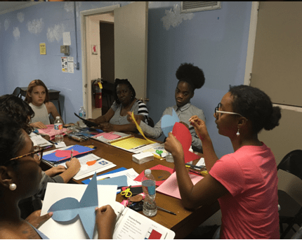 Art Facilitator Jacel Jones models the language of art, as well as the proper way to teach children how to hold scissors or a brush.